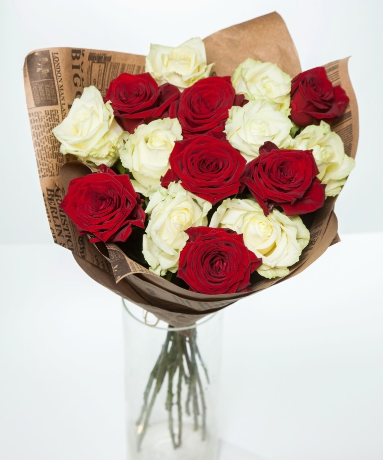 Букет из 15 красных и белых роз в крафте.
